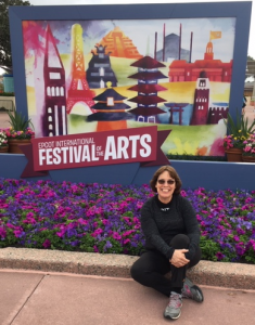 Linda Barnicott, Pittsburgh's Painter of Memories, poses in front of the Epcot International Festival of the Arts sign.