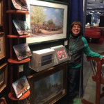This photo features Linda Barnicott, Pittsburgh's Painter of Memories, smiling next to her booth at the Pittsburgh Home and Garden Show.