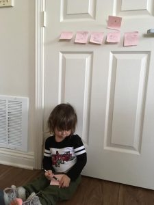 This photo features Aria Stadelman, Linda Barnicott's granddaughter, drawing while sitting on the floor. Some of her other drawings are taped to the wall behind her.
