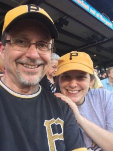 Photo description: Tom Barnicott and Alyssa Stadelman, both in Pittsburgh Pirates gear, attend a game at PNC Park.