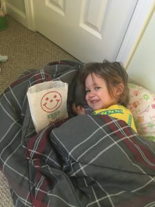 Aria Stadelman, granddaughter of Linda Barnicott, laying on the floor with an Eat 'n Park smiley cookie bag.