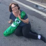 Linda Barnicott, Pittsburgh's Painter of Memories, sitting on the ground of the Clemente Bridge with a pickle balloon.