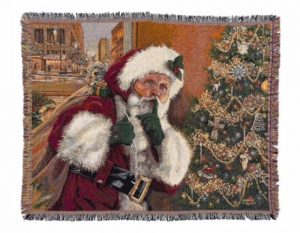 "The image shows a close up of Linda Barnicott's new throw blanket featuring her painting ""Shhh!"" Santa Claus is holding his bag of toys while standing beside a Christmas tree."