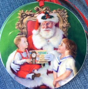 An image of Linda Barnicott's newest ornament, Wishes For Santa, featuring Santa Claus with a small boy on his lap and a young girl looking up at him.