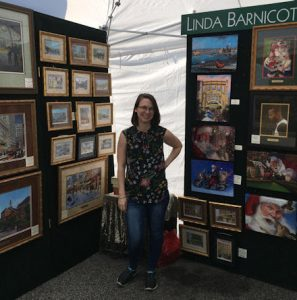 Brittany Barnicott, Linda Barnicott's daughter, poses inside of her booth at the Mt. Lebanon Artists' Market.