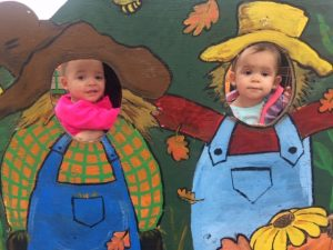 This image shows Abigail and Autumn, granddaughters of Linda Barnicott, in a scarecrow photo station at Trax Farm.