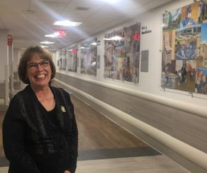 This image features Linda Barnicott posing in front of her new murals at Forbes Hospital