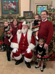 This image features Linda Barnicott, her husband, and granddaughters posing with Santa Claus.