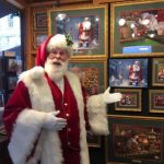 This image shows Santa Claus standing inside Linda Barnicott's chalet at the Peoples Gas Holiday Market in Market Square, Pittsburgh