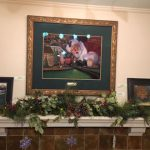 "This image shows Linda Barnicott's original painting ""All Aboard with Santa"" above the mantel in her home."