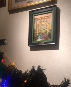"This image shows Linda Barnicott's original painting ""Pickle Fun in Pittsburgh"" hanging on the wall in her home."