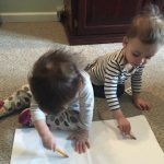 This image features Linda Barnicott's granddaughters, Abigail and Autumn (age 18 months), drawing together on a sheet of paper.