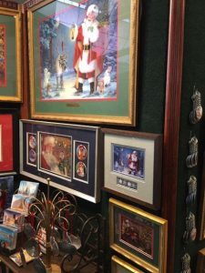 This image shows a portion of Linda Barnicott's 2020 Home & Garden Show booth, including images of her Jolly Old Elf Series (Santa's Woodland Christmas and Santa's Snowy Friends).