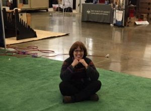 The image is of Linda Barnicott sitting down at the Pittsburgh Home and Garden Show.