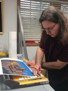 "Alex Patho, printer, works on Linda Barnicott's new painting ""Pittsburgh's Tunnel Vision."""