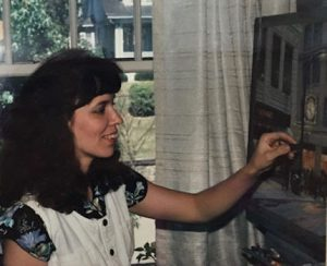"This image shows Linda Barnicott working on her painting ""Meet Me Under Kaufmann's Clock."""